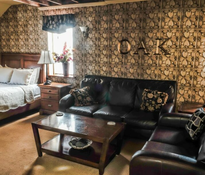 The Iowa Grand Oak Room with bed, sofas, coffee table