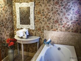 bathroom with floral wallpaper and tub