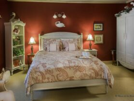 Trumpeter Room with red walls and white furniture