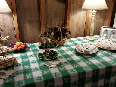 table decorated for St. Patrick's Day with green and white tablecloth and pastries