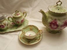 green and pink teapot, cup, saucer, creamer and sugar