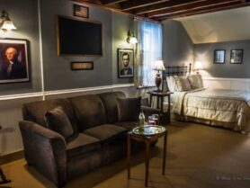 Walnut Grove room with bed and sofa, pictures of presidents on wall