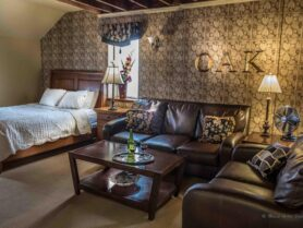 The Iowa Grand Oak Room with bed, sofas and table
