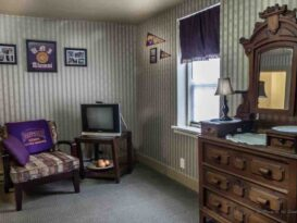room with dresser, tv, chair, striped wallpaper