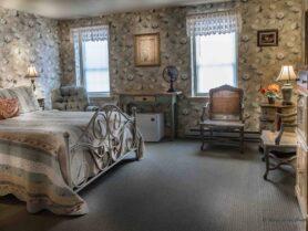 room with floral wallpaper, bed, rocker, recliner