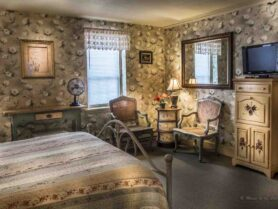 room with floral wallpaper, bed, rocke