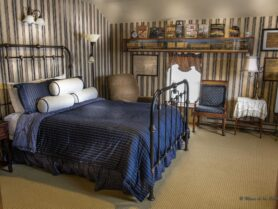 bedroom with iron bed with blue bedspread, 2 chairs