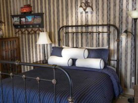 iron bed with blue bedspread
