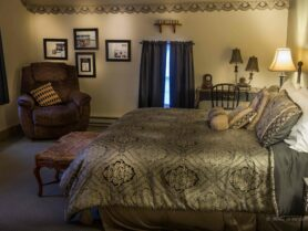 bed with brown bedspread, recliner, lamp