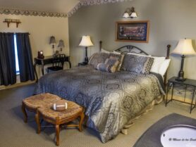 bed with brown bedspread, lamps, bench with football