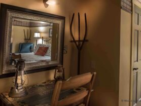 room with brown walls, desk and chair, mirror reflecting bed