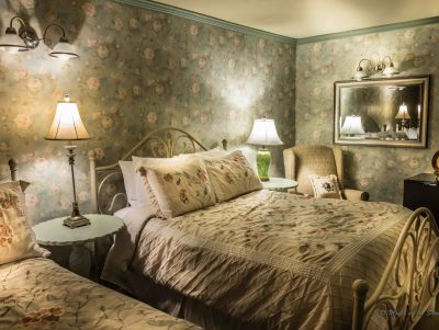 bedroom with floral wallpaper and 2 beds, lamps