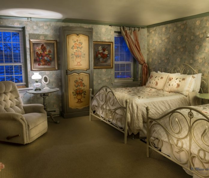 bedroom with floral wallpaper and 2 beds, lamps, recliner