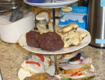 Three tiered china serving tray filled with savory ands sweet items