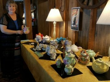 lady holding teapot next to table with teapots