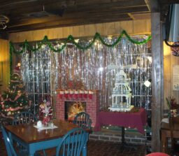 table and chairs next to wall decorated for Christmas with tree and fireplace