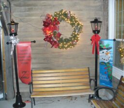 bench between 2 lanterns with wreath above