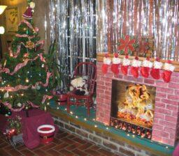 Christmas tree next to fake fireplace