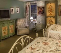 bedroom with floral wallpaper and 2 beds, recliner, tv