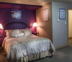bed with red wall and 2 lamps