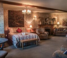 bed in room with floral wallpaper, recliner, sofa, fireplace