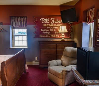 The Major Leaguer room with bed, chest of drawers, comfy chair and small fridge